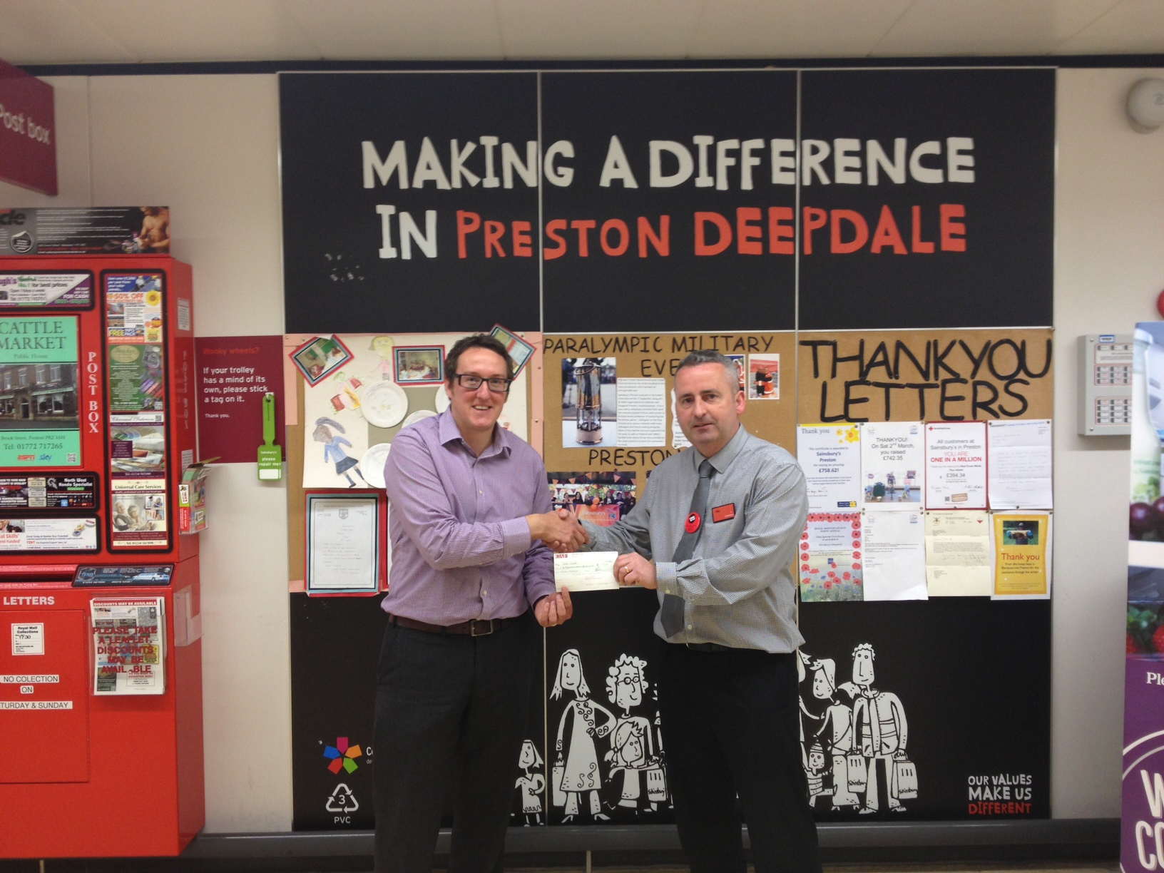 Ben Blackman receives the cheque from the Deepdale store team