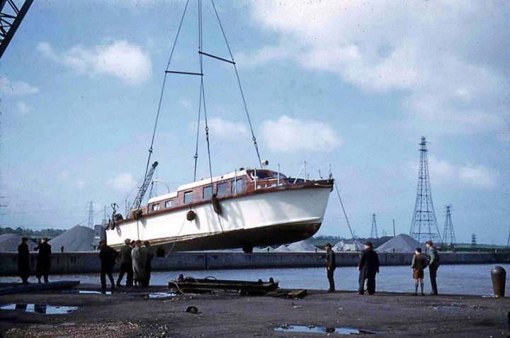 Early 1950's at Preston Dock. A gentleman's motor yacht is launched into the dock basin watched by brothers Chris and David Miller (far right). Chris later went on to found Preston Marina on the site following the closure of the dock as a commercial port.
