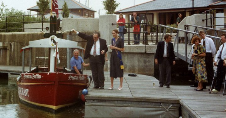 Preston Puffin is launched at Preston Marina c.1992. Preston Puffin was converted from a fishing boat in order to offer boat rides around the dock and into the river. Chris Miller, founder of Preston Marina is seen right of centre, in the dark jacket.