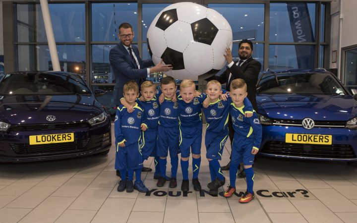 Lookers Volkswagen, Blackburn has announced a new sponsorship deal with Ribbleton FC's Green Squad, a local youth football team of boys under the age of seven that competes in the Central Lancashire League. The ambitious and determined squad of youngsters comprises of eight boys and two coaches and the team plays in numerous local tournaments from Blackburn, throughout Manchester and the North East. This sponsorship deal with Lookers will provide the team with specially designed new kits for both home and away games. Lookers, one of the UK's largest car retailers, is committed to supporting local communities through its national dealership network and this new arrangement underpins the company's values of investing in community-based projects. Pictured at the Lookers Volkswagen showroom on Trident Way in Blackburn are General Manager Paul Atkinson and New Car Sales Manager Omar Salim with Green Squad players (from L-R) Harvey Adair, Alfie Blackledge, Charlie Bond, David Driver, Kian Winrow and Lucas Jeory.