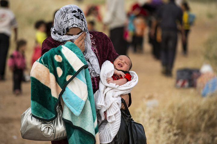 "A young mother crosses the border from Syria and becomes a refugee. She carries her one-month-old son, Hamid. ""Since he was born there has been non-stop bombing every day."" Pic: UNCHF"