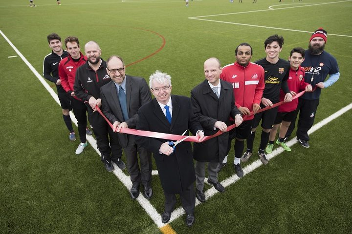 Mark Menzies MP cutting the ribbon to officially open the 3G pitch watched by student footballers, USA Duty Manager Neil Cottam, UCLan Business Services Manager Andy Coverdale and Joel Arber, Pro Vice-Chancellor of External Relations.