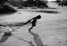A refugee pulls a water jug along