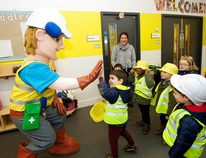 Charlie Conlon high-fives a pupil during the visit