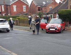 A woman is led away from the crash, with the red Mini next to a pile of bricks