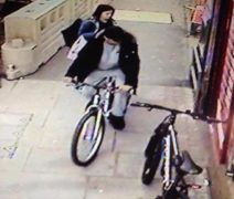 Pictures showing two people near the bike, parked outside Bargain Booze