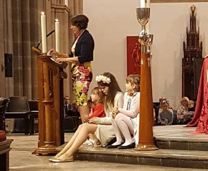 Louise Ashworth speaking at the memorial service to her husband Ben, with their daughters sat listening