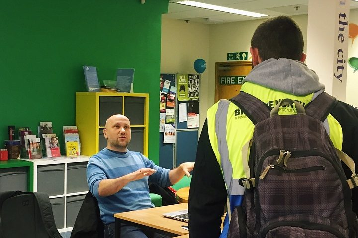 One of the UCLan volunteers speaking to a Big Issue seller