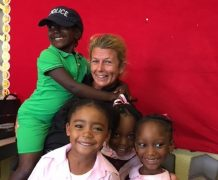 Julie with school children who she helped (and they pinched her hat!)