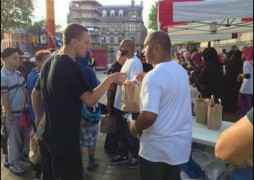 A volunteer hands out food on the Flag Market
