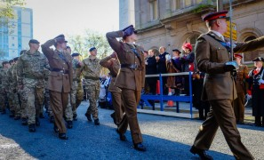 Military personnel parade past the public on the Flag Market