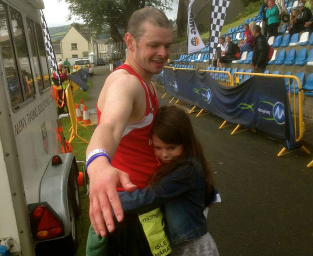 Ben gets a hug from one of his daughters after finishing the Isle of Man marathon