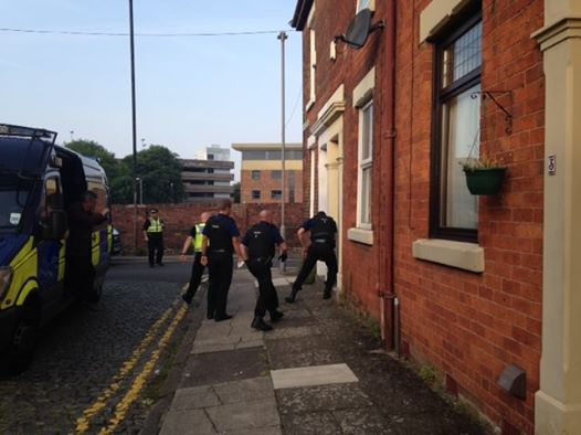 Police officers raid a house in Preston on Wednesday morning