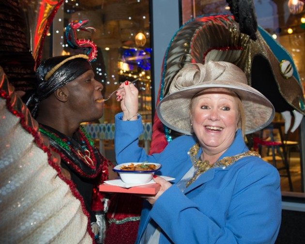The Mayoress feeds some hotpot to one of the Turtle Bay dancers