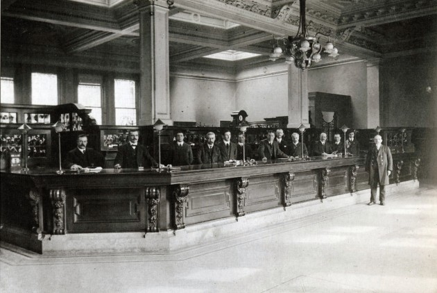 Preston Savings Bank interior c.1920 Notice the twelve tellers behind the counter and the position of one of the security gates on the right side of the counter. The upper part of the vault door can also be seen just above the rear screen in the centre of the image