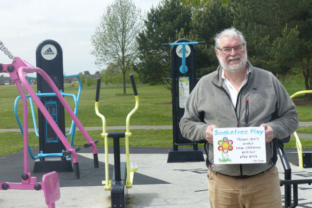Councillor Robert Boswell holding up one of the new signs in Ashton Park