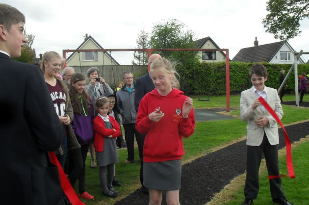 The ribbon is cut to declare the new play area open