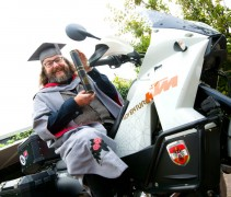 Dave Myers gets on his bike after graduating