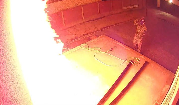 Flames from the window as one of the men watches