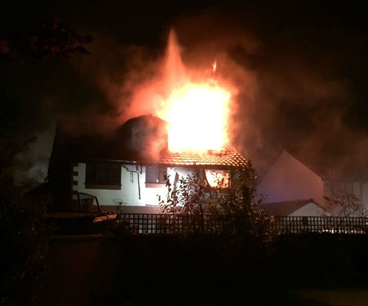 Flames can be seen coming from the house, the fire started around 4am Pic: Gavin Seed