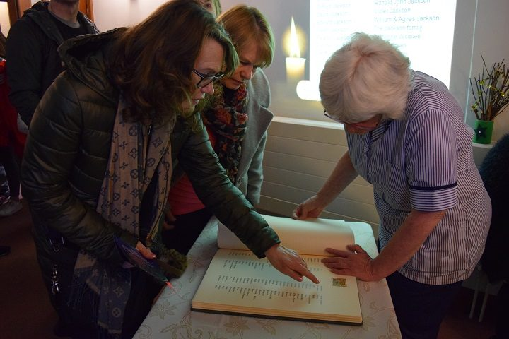 Families inspect the book of remembrance
