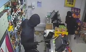 One of the men uses the crow bar to lever open the till