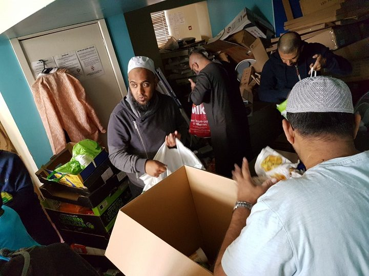 Volunteers at the mosque sorting through food items