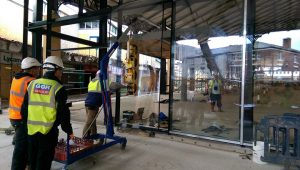 Workmen moving one of the glass panels into place at the Orchard Street end of the market