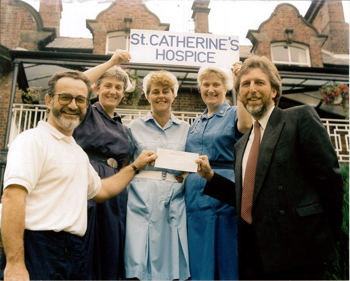 John Nickson with one of many cheques he helped source for St Catherine's