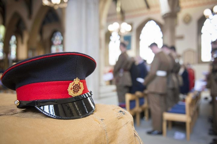 A formal dress cap and badge inside the Minster with the soldiers in the background during the service