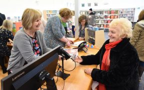 Cathy Openshaw shares a smile with Carol Green as she takes out books from the reopened library