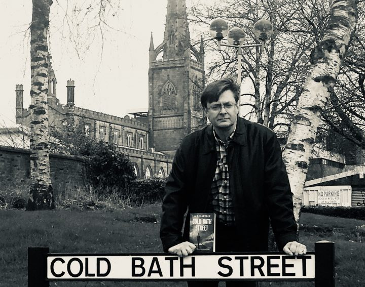 A.J. Hartley in front of Cold Bath Street sign