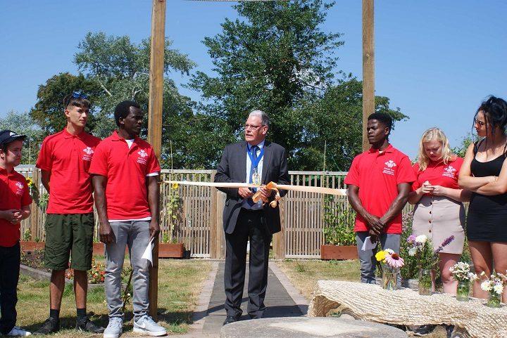 Cllr Borrow cuts the ribbon on the community garden