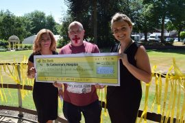Les presents his donation to St Catherine's Hospice - and sports his England beard