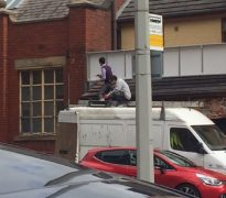 Two men were seen using the roof of a van to put up a sign Pic: Preston City Council