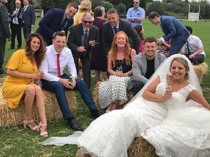 Bride Bridget poses with guests on hay bales