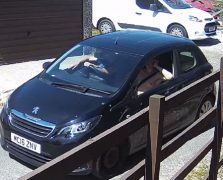 The man can be seen in the black Peugeot