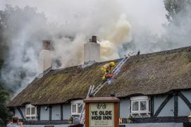 A firefighter makes his way onto the roof of the Olde Hob Inn Pic: Dave Bennion
