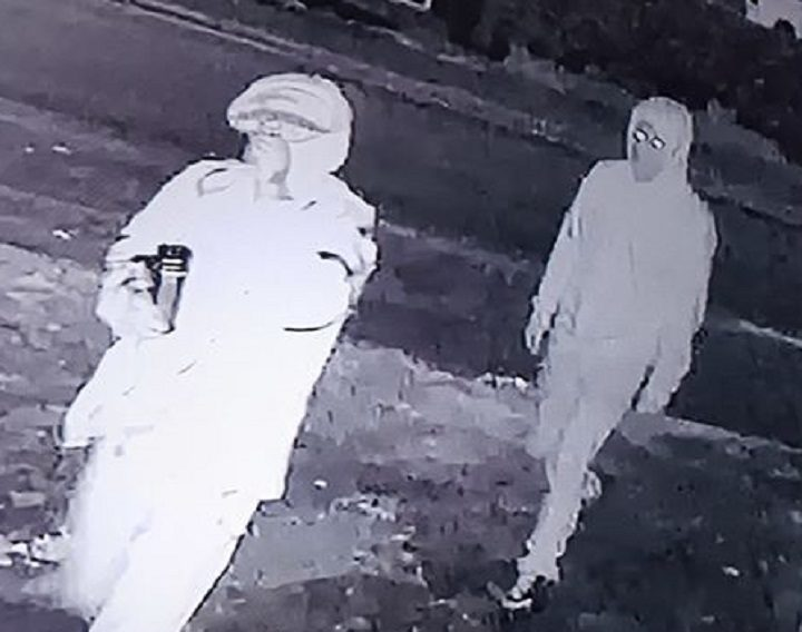 Two men are seen on CCTV approaching the garage