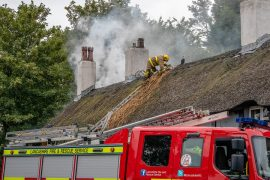 A firefighter tackling the fire in the thatch Pic: Dave Bennion