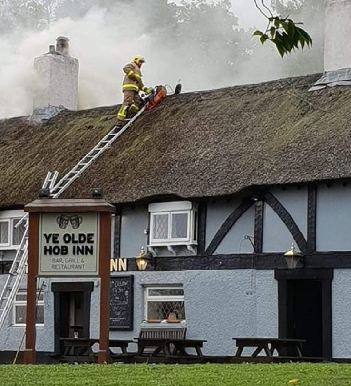 A firefighter on the thatched roof Pic: Mark Wilson