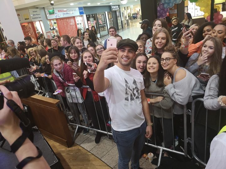Jack Fincham posing for a selfie with students in the shopping centre