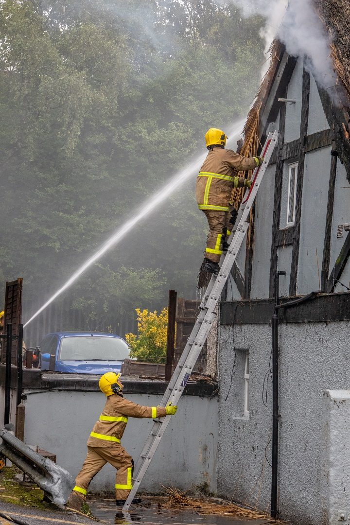 A firefighter goes up to inspect the side of the pub Pic: Dave Bennion
