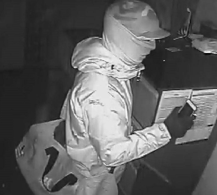One of the men holds an iPhone during the break-in