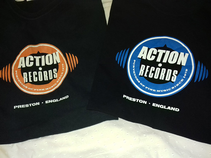 The old tangerine and new blue versions of the Action Records t-shirts