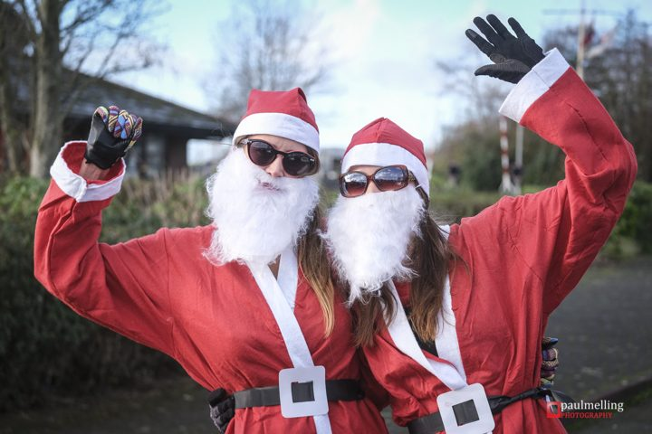 A pair of Santas pose for a picture on the run