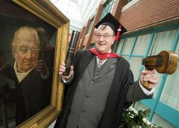 Roger at his graduation, holding a painting of ancestor Joseph Livesey