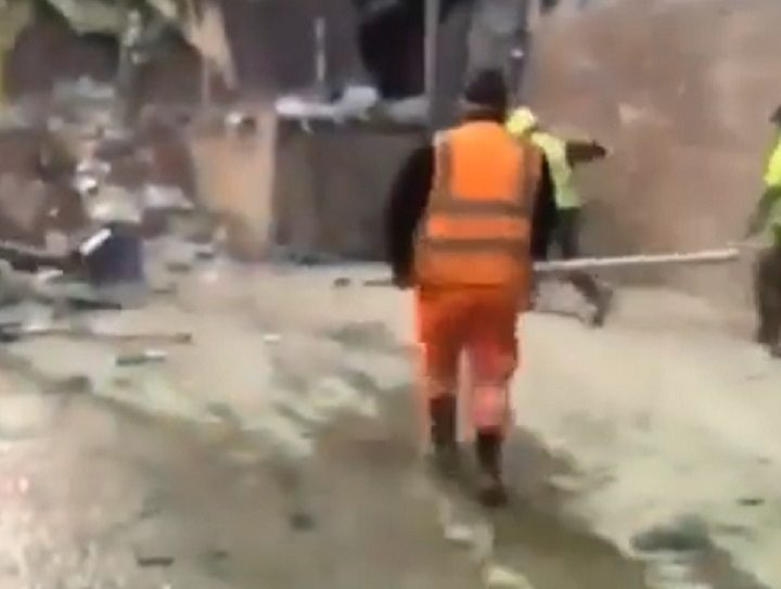 Men in hi-vis are seen attacking the rats