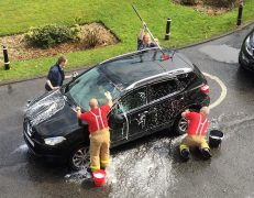 Firefighters giving a car a good scrub