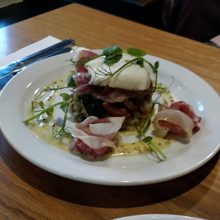 Poached egg on crushed garlic potatoes with Parma ham